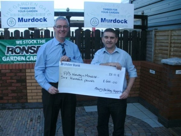 Dan Doyle Manager of Newry Building Supplies presents cheque to Seamus McCabe from PIPS Newry & Mourne