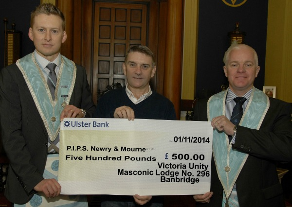 Seamus McCabe from PIPS N&M accepts a cheque from Aaron Walkingshaw ( Worshipful Master) and Charlie Marno